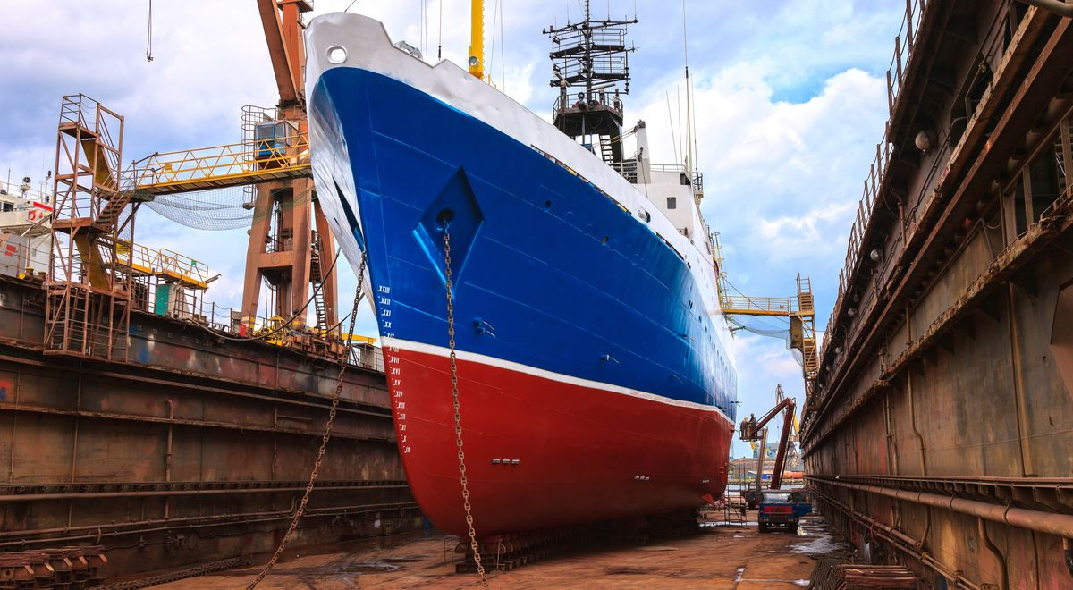 Cargo ship is being repaired in shipyard.
